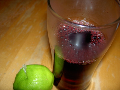a glass of hot jamaica and a dismembered lime