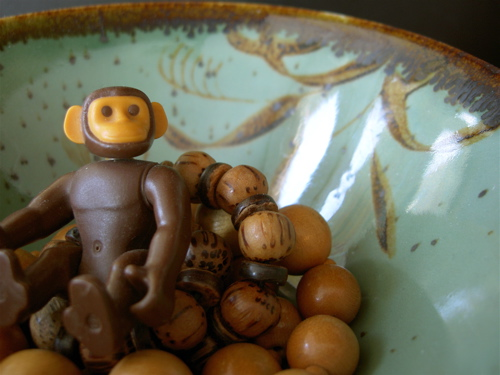 a toy monkey sitting on wooden beads in a green bowl