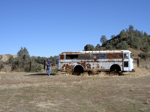 Doug looking at a rusty old bus at his uncle's ranch
