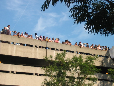 People on top of the parking structure, watching the scene.