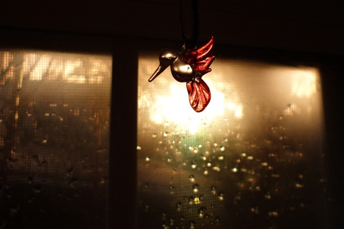 a small glass hummingbird by a window