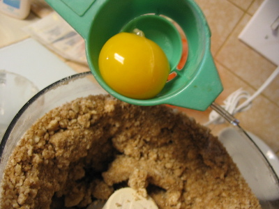 an egg yolk dropping into some toffee batter.